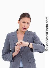 Shocked businesswoman checking her watch