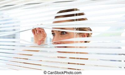 Shocked businesswoman peeking through blinds - Shocked...