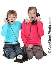 Shocked children using the telephone