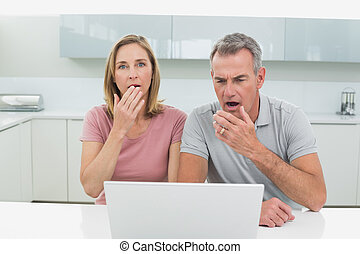 Shocked couple using laptop in kitchen