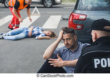 Shocked driver talking to policeman after car accident