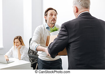 Shocked employee receiving the box with belongings from the employer
