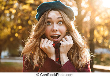 Shocked excited young pretty woman walking outdoors in autumn spring park.
