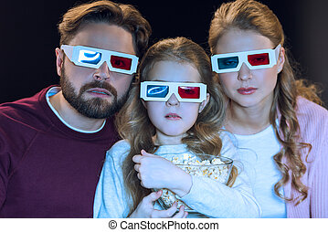 Shocked family in 3d glasses watching movie and holding popcorn