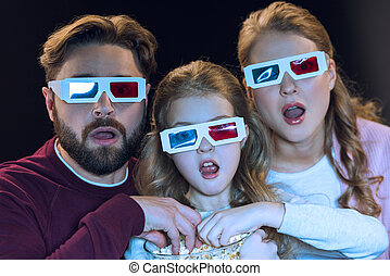 Shocked family in 3d glasses watching movie and eating popcorn from bowl