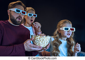 Shocked family in 3d glasses watching movie and eating popcorn