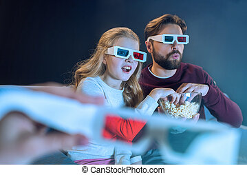 Shocked father and daughter in 3d glasses watching movie and eating popcorn