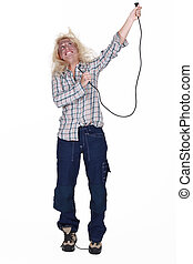 Shocked female electrician holding cable