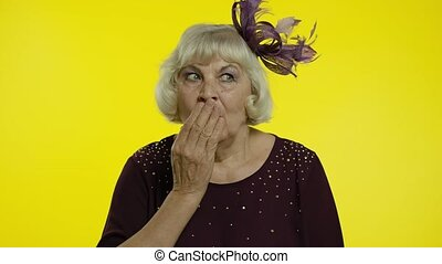 Shocked frightened senior old woman covering mouth with hand...