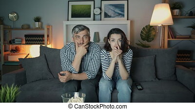 Shocked girl and guy watching TV with serious faces touching...