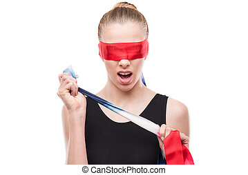 shocked gymnast in leotard with eyes covered with red ribbon isolated on white