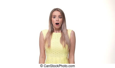 Shocked happy ginger woman in yellow dress covering mouth and looking at the camera over white background.