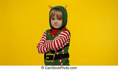 Shocked kid girl in Christmas elf Santa helper costume. Child look at camera and ask question what