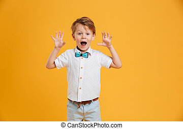 Shocked little boy child standing isolated