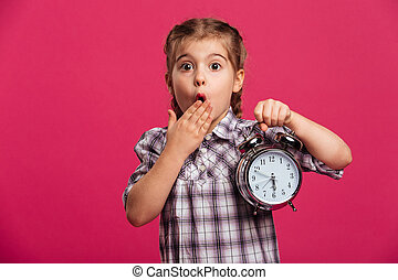 Shocked little girl child holding clock alarm. - Picture of...