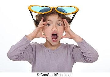 Shocked little girl wearing comedy glasses