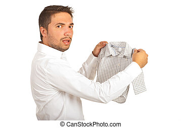 Shocked man holding shrunk shirt and looking at camera...