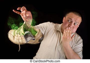 Shocked man holding smelling shoe isolated on black...