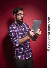 Shocked man with digital tablet