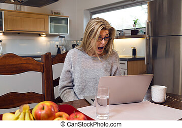 Shocked middle-aged woman with laptop