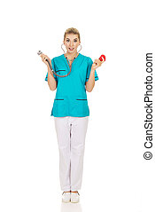 Shocked nurse or female doctor holding stethoscope and heart mod