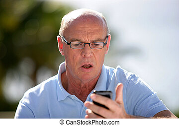 Shocked old man reading text message