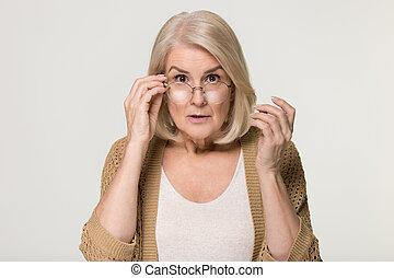 Shocked old woman in disbelief lowering glasses looking at camera