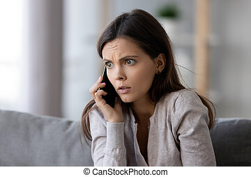 Shocked or scared young woman talking on mobile phone