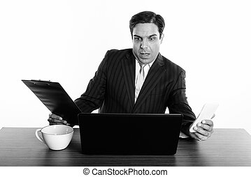 Shocked Persian businessman holding mobile phone and clipboard while using laptop with coffee cup on wooden table