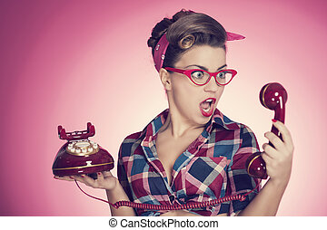 Shocked pin-up girl looking at retro telephone