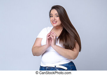 Shocked Plus Size Model with long hair posing in studio. eyes wide open and mouth.