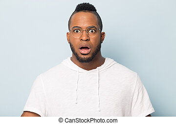 Shocked scared African American man in glasses looking at camera