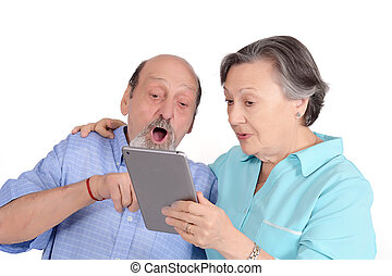 Shocked senior couple with tablet pc