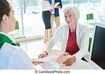 Shocked senior customer looking at bank specialist