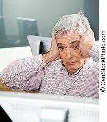 Shocked Senior Man Looking At Computer In Classroom