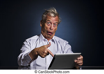 Shocked senior man pointing to his tablet computer with his finger with a look of appalled disbelief and confusion, humorous upper body studio portrait