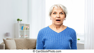 shocked senior woman with open mouth at home