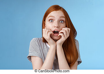 Shocked speechless gasping young redhead girl staring impressed stunned watching important moment tv series biting fingers open mouth shook standing excited blue background anticipating.