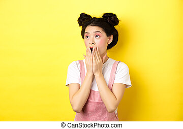 Shocked teen asian girl with makeup, gasping and covering mouth, looking left at logo amazed, standing on yellow background