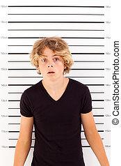 shocked teen boy taking police mug shot