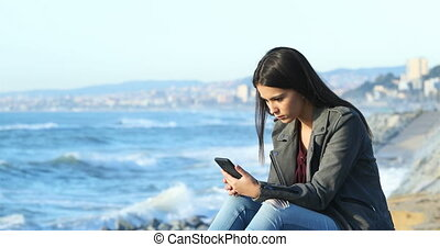 Shocked teen reading good online news on the beach - Shocked...