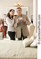 Shocked with a price. Shocked middle-aged man holding a price while standing near his wife at the furniture store