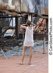 shocked woman standing in front of burned out house