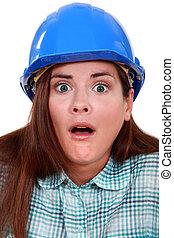 Shocked woman in a hard hat