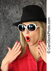 Shocked woman in sunglasses and a hat