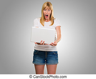 Shocked Woman Looking At Laptop against a grey background