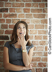 Shocked woman looking up on brick wall