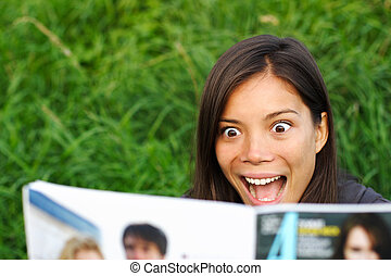 Shocked woman reading magazine - Excited woman surprised by...