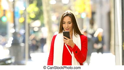 Shocked woman reading online news in the street - Front view...