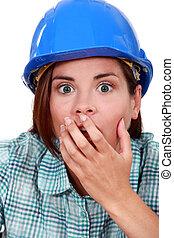 Shocked woman wearing a hard hat